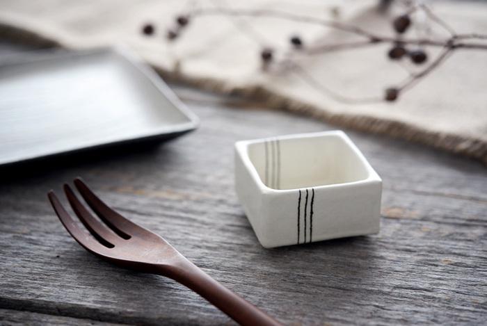 白地に十草のラインを描いたモダンな角小鉢は、信楽の文五郎窯にて作陶されている奥田 章(おくだ あきら)さんの作品です。約6cm角の小ぶりなサイズは、ちょっとしたおつまみや薬味、ディップのソースを入れるのにちょうどいい大きさです。単品使いはもちろんのこと、ワンプレートの小鉢としても活躍してくれます。