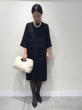 落ち着いた印象のブラックのワンピースに、ふわもこのファーバッグを合わせおしゃれ度をアップ。歩くたびにプリーツ部分が揺れて女性らしさを演出してくれます。