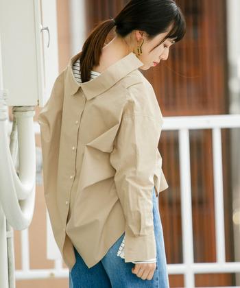 シンプルなベージュシャツのバックスタイルに、襟とボタンを施したオーバーサイズのアイテム。前から見るとシャツを後ろに抜いているような、トレンド見えする一枚です。
