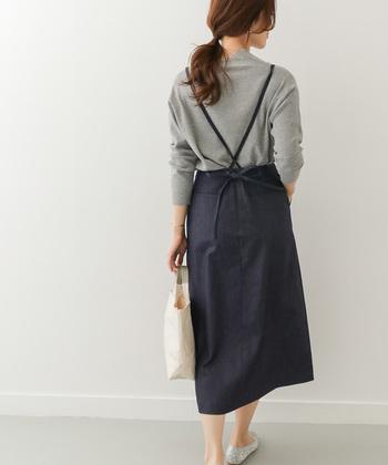 Aラインのシルエットが上品な、デニム素材のサスペンダースカートです。バックデザインはサスペンダーがクロスになっていて、さりげない繊細さをアピールできます。