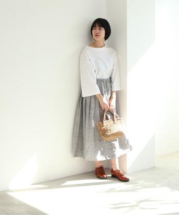 グレーベースのチェック柄スカートは、ふわっと広がるフレアシルエットで柔らかさをアピールできます。白トップスと茶色のシューズで、柔らかな雰囲気の春コーデに。