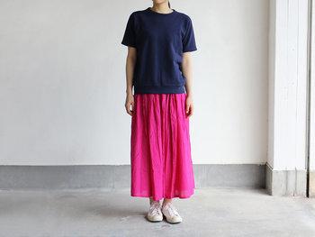 ベーシックなネイビーのTシャツに、ピンクのスカートを合わせたコントラスト強めの上級者コーデ。