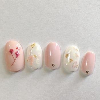 ひとつの指だけに押し花をアレンジしたシンプルネイルは、年齢を問わず使える品のいいデザインです。白ベースにシェルを入れるとシックな華やかさが生まれますね。