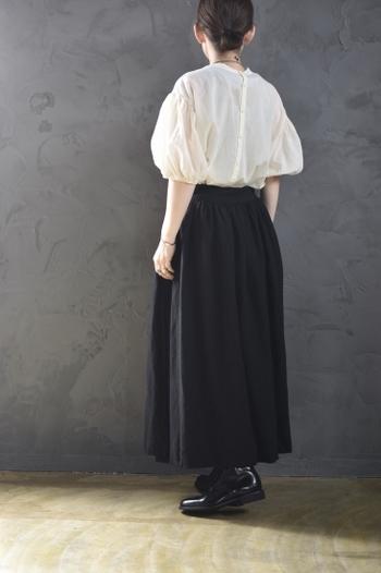 ふわっとした袖のブラウスに、シックなスカートを合わせて全体のコントラストを強調したスタイルは、チャレンジしやすいコーディネートです。バックのボタンがアクセントになって可愛さをプラスしています。