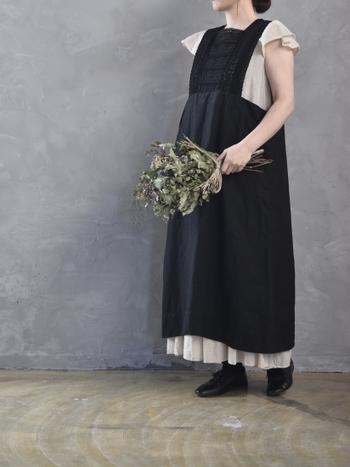 ロマンティックな白いワンピースはインナーとしても活用してみましょう。シックな黒いサロペットタイプのスカートから覗かせる袖とスカートのギャザー部分は、全体に可愛らしい雰囲気を出してくれます。