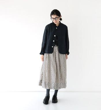 トップスと足元をかっちりとした黒でまとめて、白地にふんわりとしたドット柄のスカートスタイルも素敵です。フェミニンなデザインは、シックなものと合わせることで魅力が際立ちます。