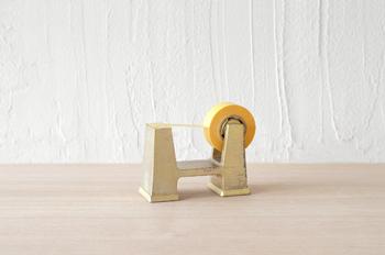片手でもテープが切りやすいように真鍮無垢の鋳物でどっしりと重く、かつ移動させやすいように下部に空間を設け、手を入れて持ち上げやすくなっています。部屋に置いてあるだけでおしゃれなオブジェのような存在感です。