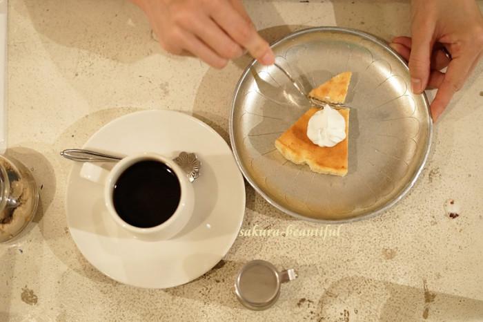 生クリームをのせたベイクドチーズケーキとコーヒーでカフェタイム。店主お気に入りの府中「南方郵便機」の自家焙煎コーヒーや、coucouのハーブティーなどこだわりのドリンクも楽しめます。