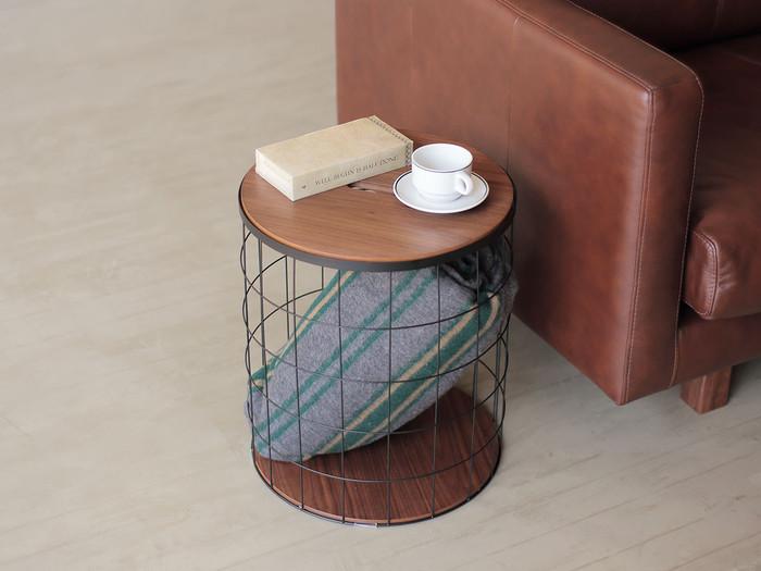 こちらはスチールのバスケットと一体化したサイドテーブル。見せる収納をユニークに楽しめるデザインです。お気に入りのブランケットをさりげなく見せるのもいいですね。