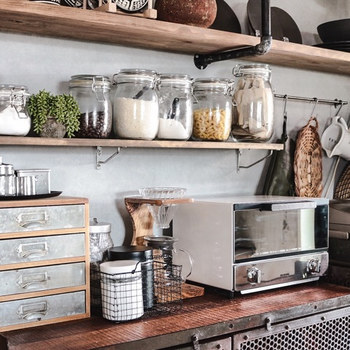 キッチンは生活感が出やすい場所ですが、見せる収納を可愛くまとめると、カフェスタイルの空間に近づきます。  例えば、こちらのお宅のように調味料や食材を統一感のあるガラス容器などに移し替えて飾るとおしゃれ。中身も一目瞭然で使いやすさもアップしますよ。