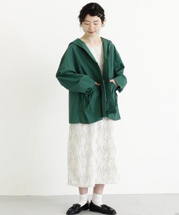 優しい雰囲気の白ワンピースには、鮮やかグリーンのフードブルゾンを羽織って春らしく。足元は黒のローファーで引き締めて。