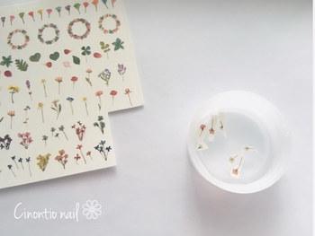 押し花シールを水に浮かべて、台紙からスライドさせて押し花の部分をはがします。ピンセットがあると便利です。