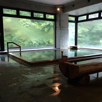 宿泊者専用の「山水の湯」です。ガラスの向こうには季節ごとに表情を変える山の風景が広がっています。露天風呂も完備されていて、自然の風に当たりながらの湯浴みもできます。