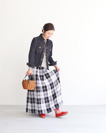 ナチュラルテイストのチェック柄スカートに、ダークカラーのデニムジャケットを合わせてシックな印象にまとめたコーディネート。足元からのぞく赤い靴の差し色が、レディな雰囲気を漂わせます。