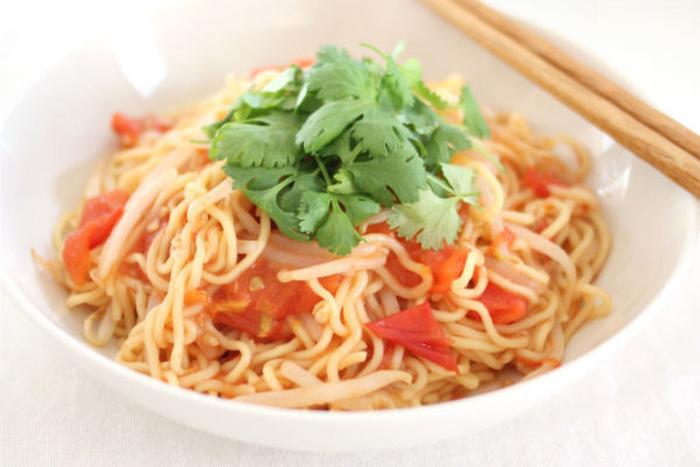 たっぷりのトマトとパクチーの蒸し焼きそば。調味料はシンプルにナンプラーだけなので、素材そのものの味や香りをたっぷり楽しめます。トマトはじっくり加熱すると、より甘さが増しますよ♪