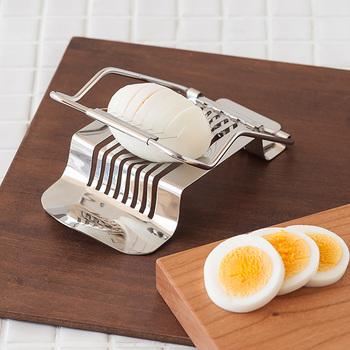 """""""エッグスライサー""""は、ゆで卵を均等な幅に素早くスライスしてくれる便利なキッチンツール。 レバーと台の間に卵をセットし、サッと引き下げるだけ。滑らかな使い心地で、簡単にゆで卵を美しくスライスすることが出来ます。サラダやカレーなどのトッピングに!丸くて可愛らしい切り口は、お子さまにもきっと喜ばれるハズ。"""