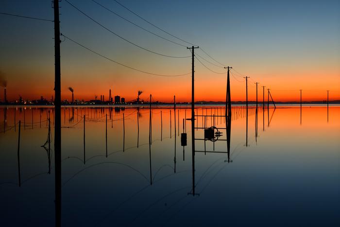 千葉県木更津市にある江川海岸は、実に不思議な風景を見ることができるエリアとしてSNSで一躍話題になったスポットです。海中に浮かぶような電柱がずらりと並ぶ様は、本当に幻想的。凪いでいるときは、その水面に電柱が水鏡となって映るところも人気の秘密です。