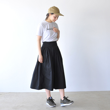"""シンプルなフレアスカートとTシャツのモノトーンコーデ。足元には存在感抜群のロングセラーモデル「M1400」のランニングスエードスニーカーを。今年のニューカラー""""black olive""""を合わせてスポーティーにまとめましょう。"""