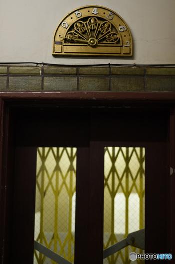 今ではほとんど見かけることのない手動式エレベーターが残っているのも、ここならでは。  停止階を矢印で示すインジケーターも当時のままで、フロアごとにデザインが異なります。作り手の遊び心が感じられますね。