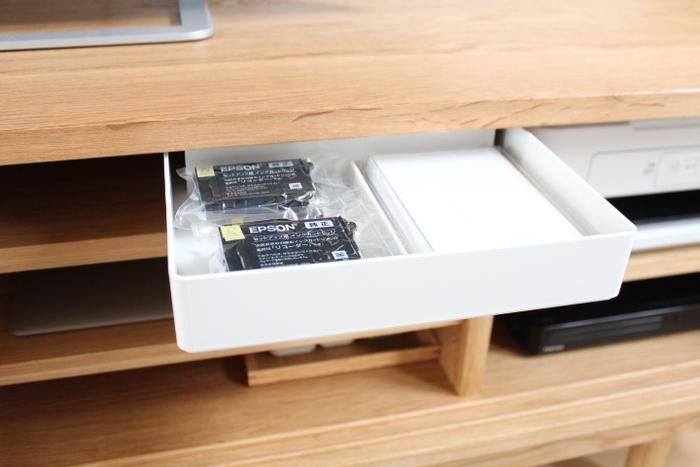 薄いものしか入らないテレビボードには、トレーで寝かせて収納するのがぴったり。プリンター用品を収納しています。