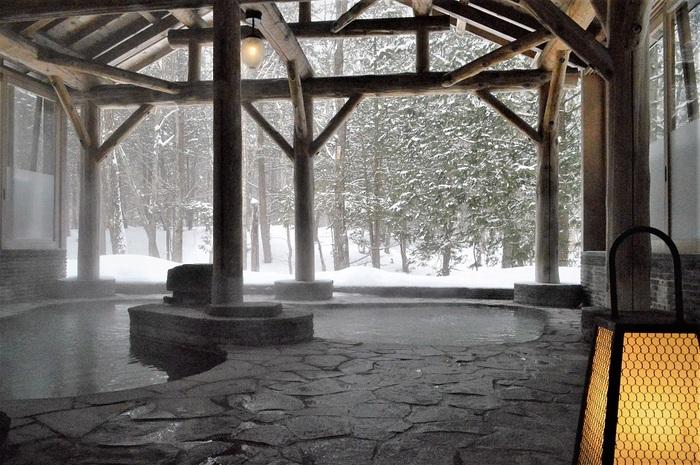 「森の湯」にある岩露天風呂「きつね・たぬきの湯」。木造りの質感が岩の肌触りと融合した素敵な露天風呂です。森に囲まれていて、四季折々の自然の景色と吹く風を感じながらで森林浴効果抜群です。