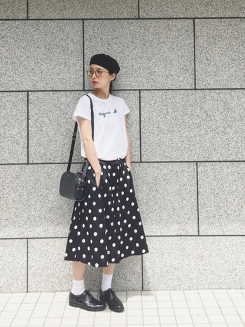 agnes b.のシンプルなロゴTシャツと、ドットプリントのスカートを組み合わせたおしゃれな大人カジュアル。Tシャツ×スカートの定番スタイルも、ベレー帽やメガネをプラスすることで上品な雰囲気漂うフレンチシックな装いに。白×黒のシンプルな配色も大人っぽい雰囲気で素敵ですね。