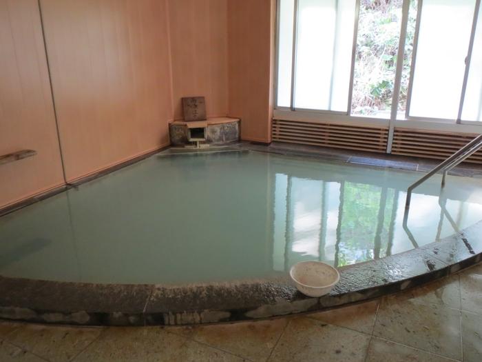 うっすら硫黄のにおいが漂う、扇形の湯舟の「白泉の湯」。白く濁ったお湯には白い湯の花が沈んでいて温泉の効果が期待できそうですね。