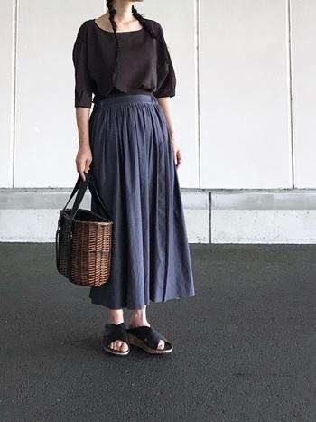 ふんわりブラウスとフレアスカートの女性らしい組み合わせ。足元にはメンズライクなレザーサンダルを持ってきて、装いに適度なインパクトを。