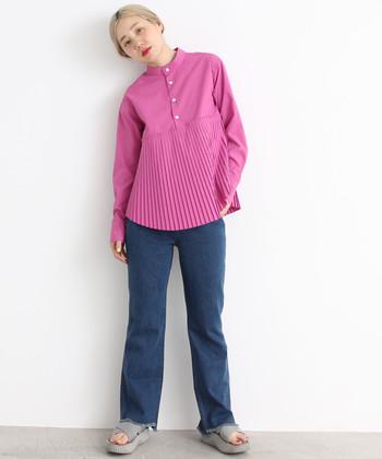 プリーツデザインがインパクト抜群なピンクのブラウスは、シンプルなデニムパンツと合わせて派手になり過ぎないようコーディネート。強めのピンクを主役にしたスタイリングです。