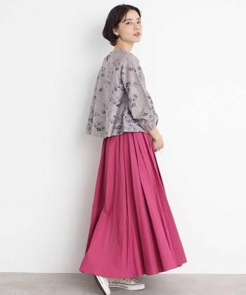 ピンクのサーキュラースカートに、グレー調の花柄ブラウスを合わせたコーディネート。パッと目を惹くピンクと対立しないよう控えめのトップスを選びつつ、花柄でテイストを合わせているのがポイントです。