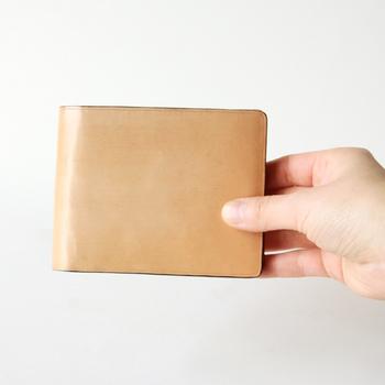 シンプルで洗練された、上品なツヤ感のあるベージュの二つ折り財布です。使う程にツヤが増していくので、経年変化によるアンティークカラーが楽しめます。