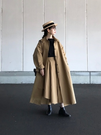 短めのツバのカンカン帽は、顔周りの髪を束ねて、大ぶりのピアスと合わせると大人な印象に。ベージュトレンチコートとスカートでトーンをまとめた洗練されたお出かけスタイルです。