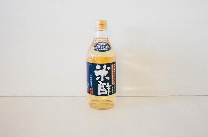 """職人さんの魂を感じさせるネイビーの背景に筆文字の「江崎酢醸造元」の""""無農薬合鴨米 米酢""""は、デイリーに使える値段も嬉しい調味料。合鴨米を自社の発酵技術で丁寧に熟成させて作られた米酢です。丸みのある酸味なので、お子様がいるご家庭でも使えます。"""