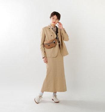 薄いベージュが上品なジャケット&タイトスカートのセットアップ。あえて真面目感を崩すように、スポーティーなボディバッグをON!