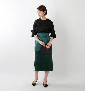 いつもより華やかさが求められる特別な日は、光沢が美しい緑のタイトスカートで。トップスと小物はブラックで統一してシックに。