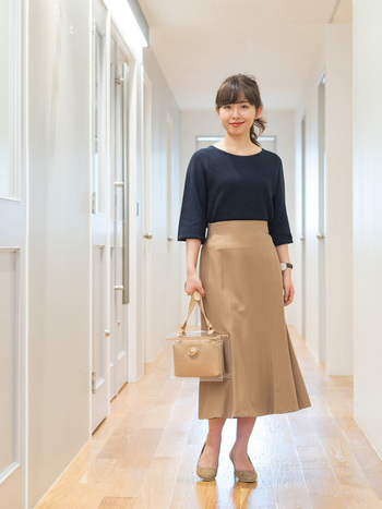 膝下丈のフレアスカートはハイウエストで穿くと大人っぽい着こなしに。ネイビー×ベージュの組み合わせが落ち着いた印象を与えてくれます。