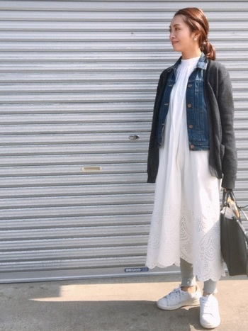 清潔感のある真っ白なワンピースに、デニムジャケットを羽織り、さらにカーディガンをかさねたワンランク上のレイヤードコーデ。足元はスニーカーでカジュアル感を出して、全体のバランスを甘くなりすぎないように上手に整えた上級コーデです。