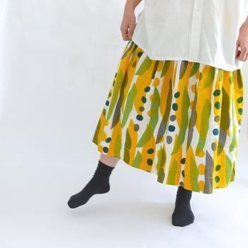 一見植物には見えないですが、実はなた豆をデザインしたスカートなんです。 デフォルメされたユニークな柄がやさしくナチュラルな印象。 黄色と緑のハーモニーも明るくさわやかで春らしい1枚です。