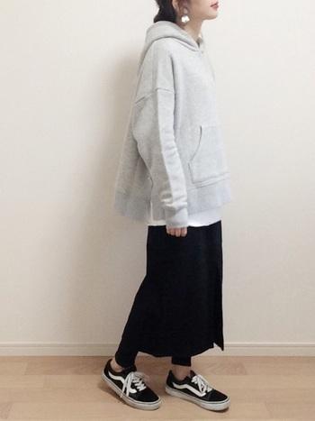 スリットデザインが可愛いパーカーにブラックデニムのスカートを合わせて。 白のカットソーをチラ見せして上下をなじみ良く。