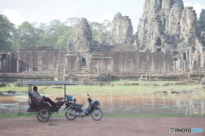 カンボジアでは、このようなバイクにつないだ席に乗る形のトゥクトゥクが主な移動手段になります。広大な敷地のアンコール遺跡群を効率よく廻るには、トゥクトゥクのチャーターが便利です。  冬に行ってもやはり暑いカンボジアですが、トゥクトゥクでじかに風にふかれながら移動するのは、楽しいひと時です。