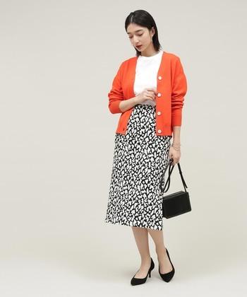 こちらはビビッドなオレンジのカーディガンに、シックなプリントスカートを合わせたエレガントなスタイリングです。カーディガン以外は白×黒のモノトーンでまとめることで、鮮やかなオレンジの美しさがいっそう引き立ちます。