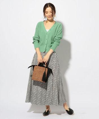 こちらは淡い色味のグリーンのカーディガンに、プリントスカートを合わせたきれいめカジュアル。深いVネックデザインのカーディガンが大人っぽい雰囲気です。爽やかなグリーンにナチュラルなかごバッグを組み合わせて、ヘルシーで女性らしいスタイリングを楽しんでみませんか?