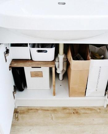 木板で作ったL字棚が設置され、上段のIKEAのボックスには歯磨き粉、ボディソープ、入浴剤などのストック品が収納されています。 下段のニトリのボックスには、シャンプー、リンス、ヘアケア製品などをまとめて。 色味が白やナチュラルカラーで統一されていることで、落ち着いた温かみのある空間に仕上がっています。