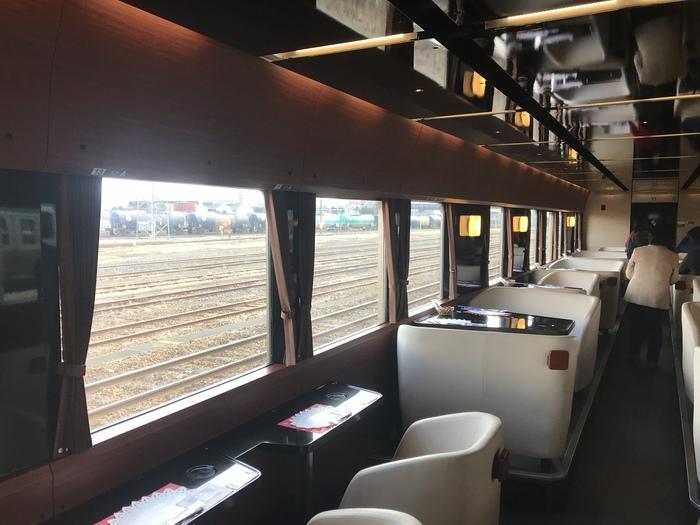 """別名""""走るカフェ""""とも呼ばれる列車の車内では、地元産のフルーツで作ったオリジナルスイーツやドリンクが味わえます。白を基調としたソファやボックス席は、高級感がありゆったりとくつろげます。"""