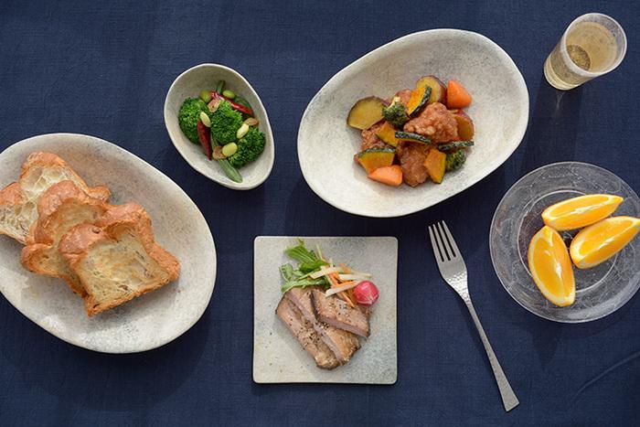 オーバル、角、丸がバランスよく配され、変化に富んだコーディネート例。グレーは赤や緑、黄色などどんな色の食材とも相性が良く、白よりも温かみがあるためコントラストが柔らかくなり、落ち着いた食卓に仕上がります。