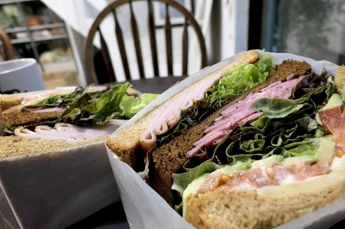 """厚さ10㎝以上もあるサンドイッチは、まさに""""萌え断""""。こちらの「ハングリー・ユアン」はターキーやパストラミ、アボカドなどにBBQソースがかかった個性的な1品です。ほかにも、ヘルシーでボリュームのあるメニューが揃っています。"""