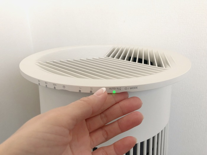 """この空気清浄機にあるのはモードを選べる電源ボタンと、タイマーボタンの2つだけ。ボタンがあると、それだけで「メカ」っぽく見えてしまいますが、この製品のボタンは天板の裏にあるため目立たず、ナチュラルなMiyokoさんのおうちにも自然と馴染んでいます。  運転モードは「AUTO・花粉・静音・標準・急速」の5パターン。Miyokoさんのおうちでは、お部屋の状態を内蔵されている""""においセンサー""""と""""ほこりセンサー""""で検知しながら、自動で風量を切り替える「AUTO」で稼働しています。 この空気清浄機を使い始めてから、花粉症だった娘さんの症状が目に見えて軽くなるという嬉しい変化があったそうです。「他の空気清浄機を使っていたときは、本当に効いているのかな?と半信半疑だったのですが…この空気清浄機は特に花粉モードに設定しなくても、AUTOモードで充分に効果を実感することができました」と話してくれました。"""