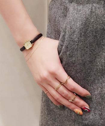 オクタゴンのフェイス×ダークブラウンの型押しレザーベルトにゴールド使いがさりげなく個性的な、ミニマルデザインのリストウォッチ。リューズにあしらわれたダイヤモンドが、さりげない上質感をプラス。