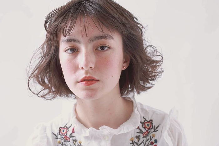 コーラルピンクのチークをふんわり頬に広めに入れると、少女のようなあどけない雰囲気に。 鼻筋を横断するように薄っすらのせるのもポイントです。