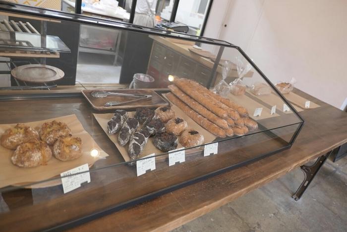 ハード系のパンが並べられ、店内もシンプル。ガラスの奥ではパンをつくっている姿を見ることができるかもしれません。